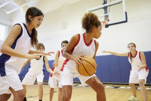 teen girls playing basketball