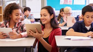 teacher demonstrating technology to student