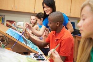 a visual arts class - teacher guiding teen boy