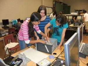 Three kids fixing a computer