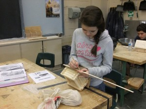 Another girl working on a wooden project