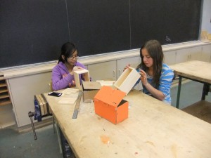 Two girls working on a wooden project