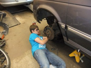 Student checking calipers on a car