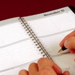 Person writing in daily agenda