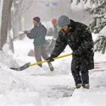 People shovelling snow in a storm