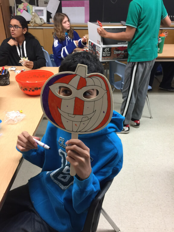 Student holding a face mask in the front of their face