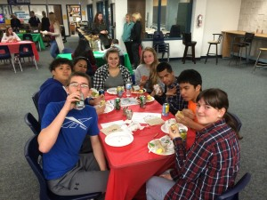 Eight students at a table eating