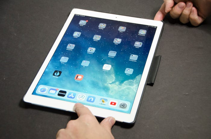 iPad with hands pressing both the power button and the home button simultaneously